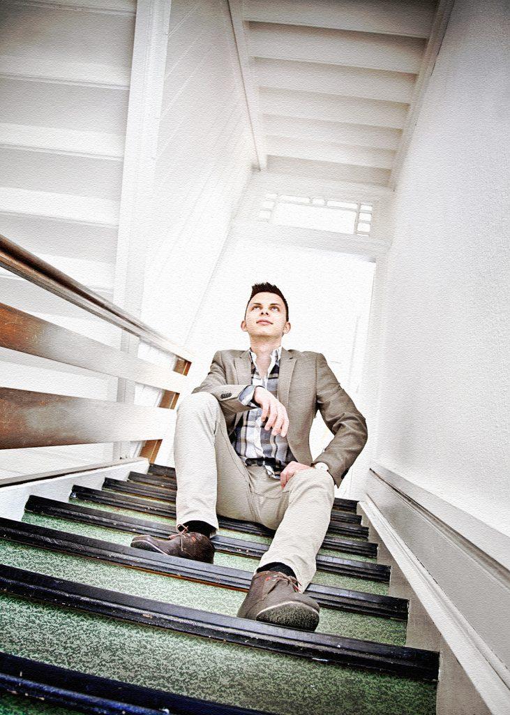 Portrait eines jungen Mannes auf den Stufen meines Treppenhauses sitzend