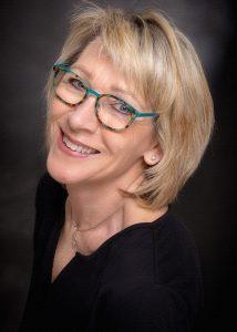 Bewerbungsfoto einer blonden Frau mit Brille und schwarzem Oberteil