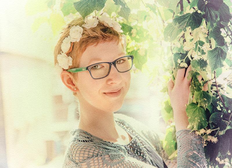 junges Mädchen mit Blumenkranz im Haar und Bluemnhintergrund
