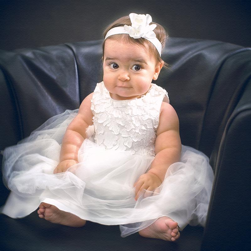 Baby im Taufkleid sitzend suesser Blick
