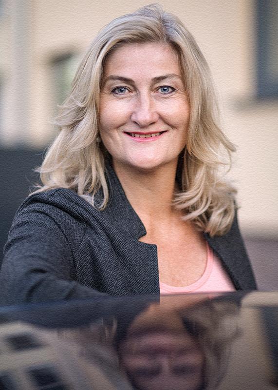 Portrait einer blonden Frau mit Spiegelung im Autodach