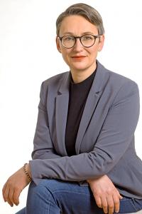Bewerbungsfoto einer Frau mit kurzen Haaren und Brille, grauem Sakko und dunklem Rollkragenpullover und starker Persönlichkeit