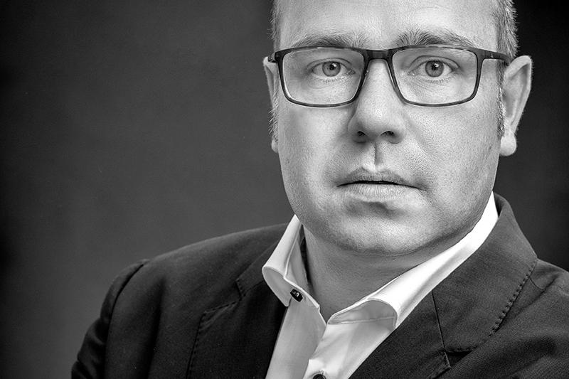 haedshot oder Bewerbungsbild eines Mannes mit Brille in schwarz/weiss mit Sakko und Hemd für Führungstättigkeit in einem Unternehmen