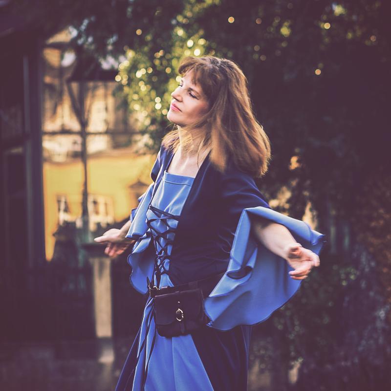 Portrait einer Frau verträumt drehend in einem blauen Kleid
