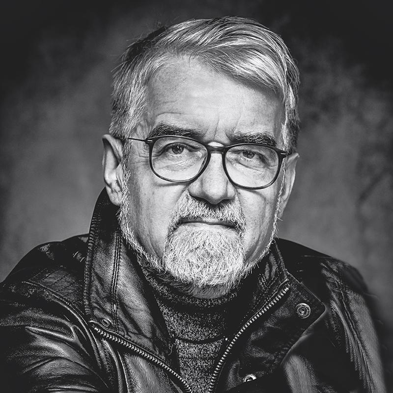 Mann mit Bart und Brille mit schwarzer Lederjacke schwarz/weiß