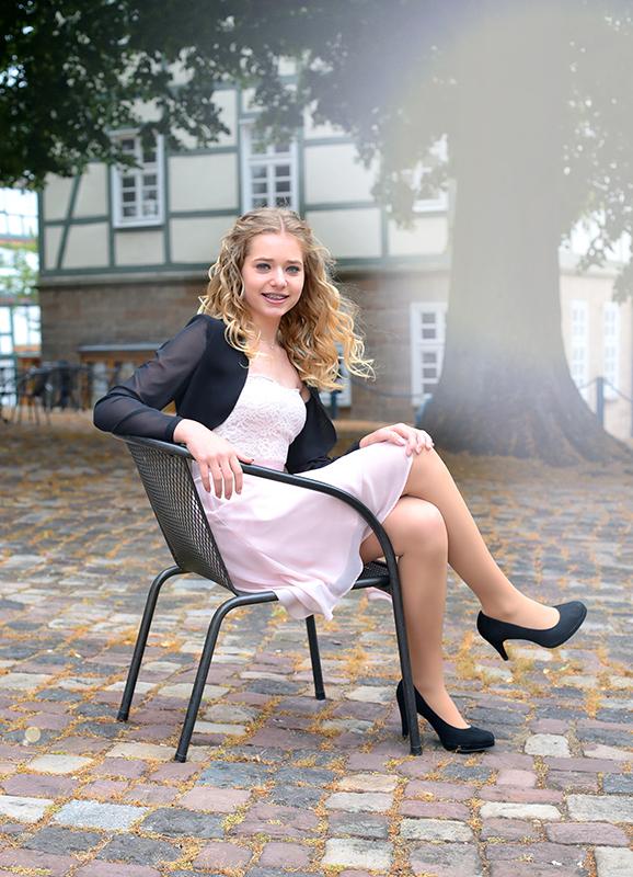 Mädchen seitlich auf Stuhl sitzend  an Mengeringhäuser Kirche zur Konfirmation