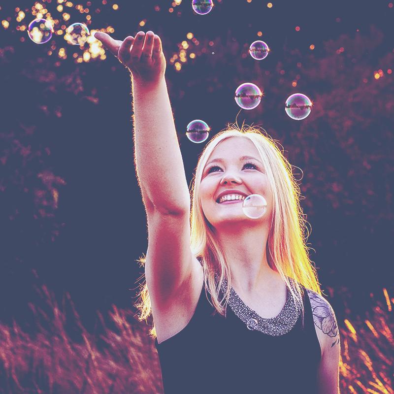 Portrait einer jungen blonden Frau im Gegenlicht mit Seifenblasen