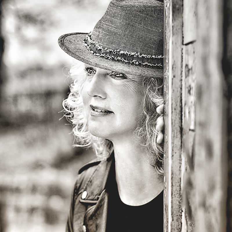 Portrait einer blonden Frau mit Locken und Hut auf dem Kopf. Seitlich in die Ferne blickend