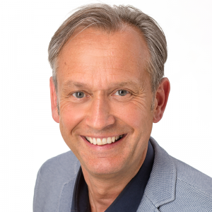 Bewerbungsbild eines Mannes mit hellgrauem Jacket und schwarzem Hemd ohne Krawatte