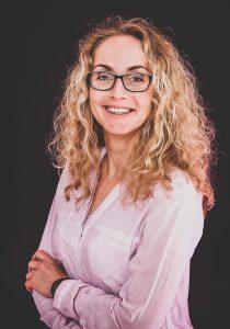 Bewerbungsbild einer blonden langhaarigen Frau mit Brille und rosa Bluse
