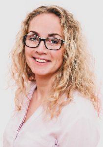 Bewerbungsfoto einer blonden Frau mit gelockten langer Haaren und Brille, rosa Bluse auf hellem Hintergrund
