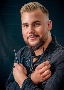 Bewerbungsfoto eines jungen Mannes mit Bart und moderner Frisur als Friseur