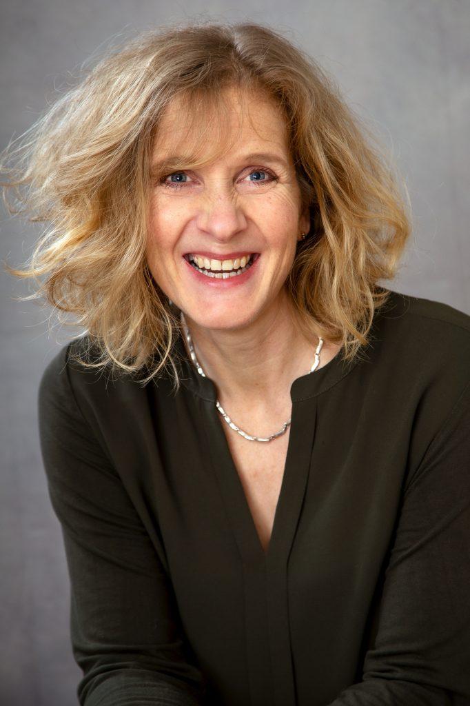 Bewerbungsfoto einer blonden Frau im Studio Aurelia Schulz lachend für einen Job in der Verwaltung